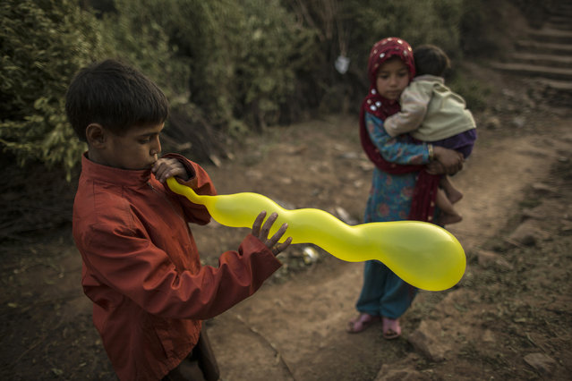 A boy inflates his balloon near a girl carrying her sibling at the entrance on the outskirts of Islamabad January 1, 2015. (Photo by Zohra Bensemra/Reuters)