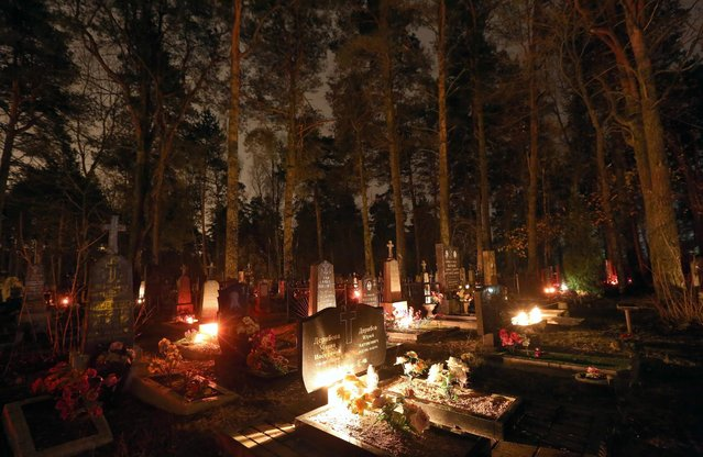 Candles illuminate graves on All Saints' Day at a cemetery in Rakov, some 45 kilometers from Minsk, Belarus, 01 November 2016. Belarussian Catholics visit graves of their relatives on All Saints Day. (Photo by Tatyana Zenkovich/EPA)