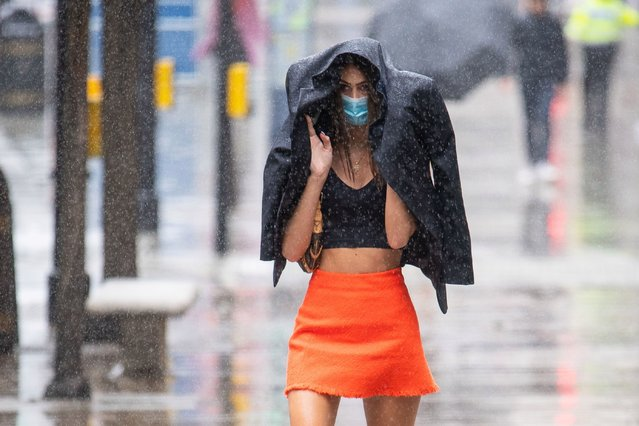 A shopper gets caught in a heavy downpour of rain on Oxford Street, London on June 27, 2020, as sunshine and showers are forecast for much of England and Wales on Saturday, with temperatures expected to hover around 22°C (71.6F). (Photo by Dominic Lipinski/PA Images via Getty Images)