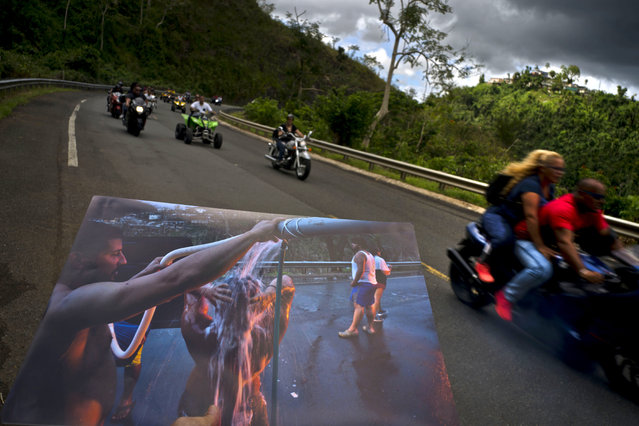 A printed photograph taken on September 28, 2017 shows people bathing on the highway after Hurricane Maria destroyed people's homes, held up at the same spot of the highway where motorcyclists ride past in Naranjito, Puerto Rico, May 27, 2018. Thanks to the owners of the land alongside the highway, creek water was piped to the side of the road for people without water to use for bathing, washing clothes and dishes. (Photo by Ramon Espinosa/AP Photo)