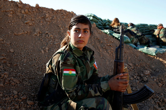 An Iranian-Kurdish female fighter holds her weapon during a battle with Islamic State militants in Bashiqa, near Mosul, Iraq on November 3, 2016. (Photo by Ahmed Jadallah/Reuters)