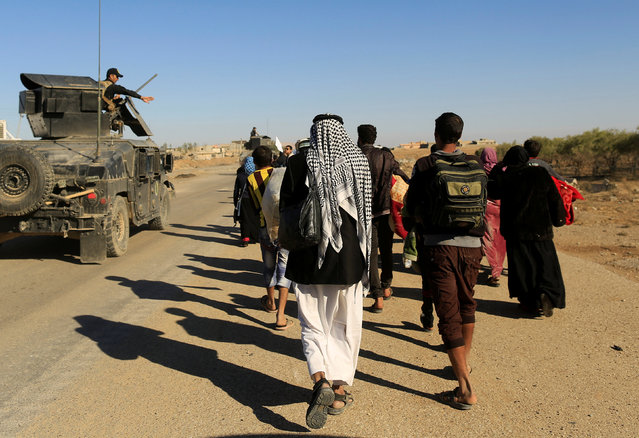 People who just fled Kokjali near Mosul walk along the road on their way to a camp for the displaced, east of Mosul, Iraq November 3, 2016. (Photo by Zohra Bensemra/Reuters)