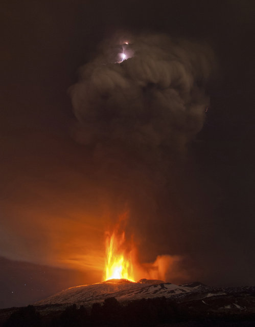 In this picture made available Friday, December 4, 2015, lightning is seen in the cloud of smoke during an eruption of Mt. Etna, near Catania, Italy, Thursday December 3, 2015. Mt. Etna is Europe's most active volcano at 3,350 meters (10,990 feet) and erupts quite frequently. (Photo by Salvatore Allegra/AP Photo)