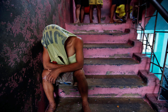 An inmate covers his head as he passes the time inside Quezon City Jail in Manila, Philippines October 19, 2016. (Photo by Damir Sagolj/Reuters)