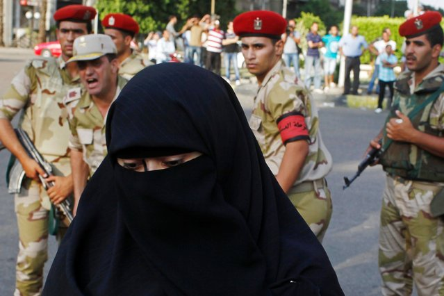 Army soldiers ask a female supporter of overthrown President Mohamed Mursi to take her protest to the sidewalk, on July 5, 2013. (Photo by Asmaa Waguih/Reuters)