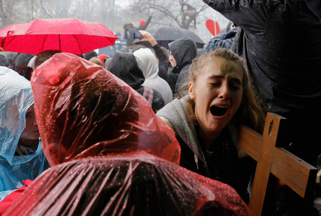 """A young woman with a crucifix cries as police use a water cannon to disperse protesters demonstrating against measures imposed by the German government to limit the spread of the novel coronavirus, on November 18, 2020 close to the Reichstag building housing the Bundestag (lower house of parliament) in Berlin. - After repeated warnings for the crowd to put on face coverings went unheeded, police said they would take action to clear the protest and """"detain violators"""". Around 5,000 activists massed at the Brandenburg Gate, after the German government banned rallies outside parliament because of fears of violence. The demonstration mirrored similar protests seen across Europe against restrictions opponents see as a violation of their civil rights despite government warnings about the need to stop the spread of infections. (Photo by Odd Andersen/AFP Photo)"""