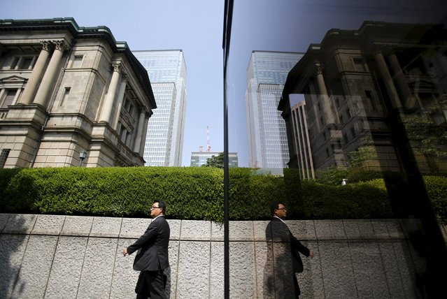 A pedestrian walks past the Bank of Japan building in Tokyo, in this May 22, 2013 file photo. The Bank of Japan is expected to make a policy decision this week. (Photo by Yuya Shino/Reuters)