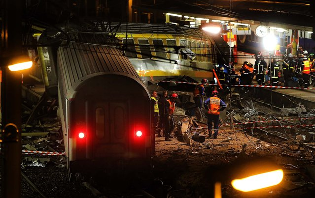 A packed passenger train skidded off its rails in Bretigny sur Orge, south of Paris, on July 12, 2013, leaving at least six people dead and dozens injured as train cars slammed into each other and overturned, authorities said. (Photo by Michel Euler/Associated Press)