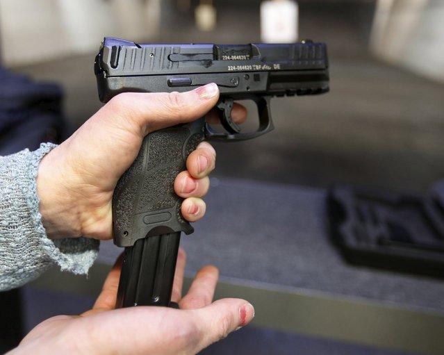 First time gun owner, Jessie Palmieri loads a clip into a H&K VP9 9mm gun at the Ringmasters of Utah gun range, in Springville, Utah on December 18, 2015. (Photo by George Frey/Reuters)