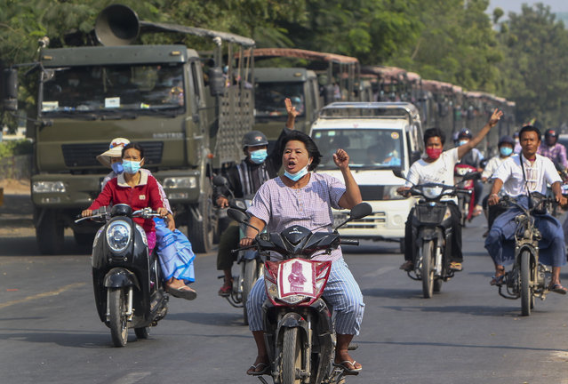 Demonstrators on motor bikes flash the three-fingered salute against the military coup as they ride pass military vehicles parked along a road in Mandalay, Myanmar on Wednesday, February 17, 2021. The U.N. expert on human rights in Myanmar warned of the prospect for major violence as demonstrators gather again Wednesday to protest the military's seizure of power. (Photo by AP Photo/Stringer)