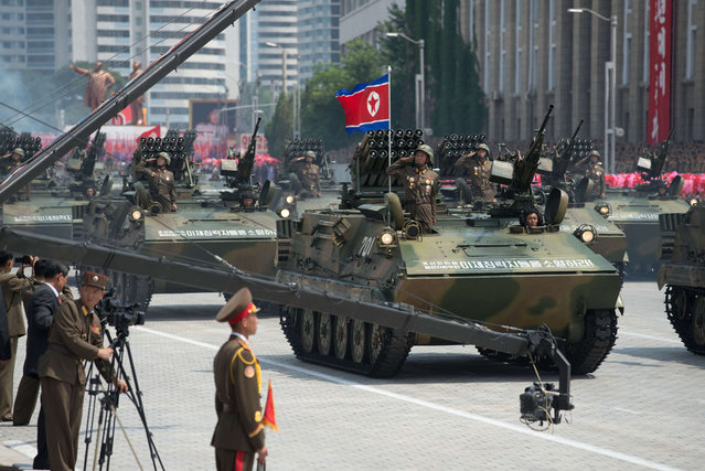 North Korean soldiers salute from a tank during a military parade past Kim Il-Sung square marking the 60th anniversary of the Korean war armistice in Pyongyang on July 27, 2013. (Photo by Ed Jones/AFP Photo)