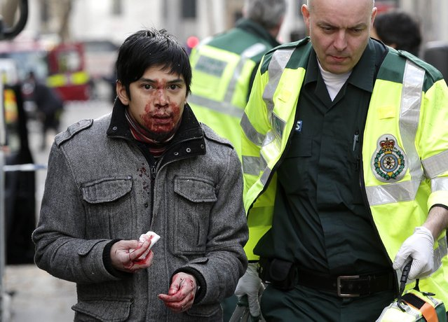 An injured man is helped by a paramedic at the scene of a bus accident on the Kingsway in central London February 2, 2015. (Photo by Peter Nicholls/Reuters)