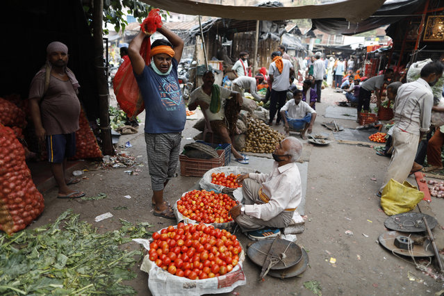 Vegetable vendors wait for customers early morning at a wholesale market in Lucknow, India, Saturday, September 12, 2020. Millions lost their jobs, and thousands, fearing starvation, poured out of cities to try and get back to their rural homes during India's lockdown of 1.3 billion people earlier this year. The economy shrunk by nearly 24% in the last quarter, the most of any major country. (Photo by Rajesh Kumar Singh/AP Photo)