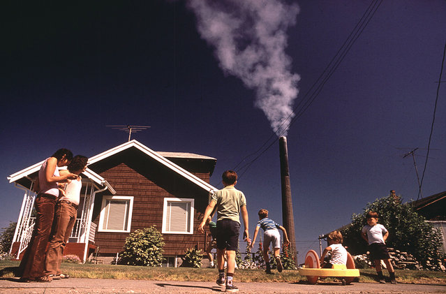 Children play in the yard of a Ruston, Washington home, while a Tacoma Smelter stack showers the area with arsenic and lead residue, August, 1972. (Photo by Gene Daniels/NARA via The Atlantic)