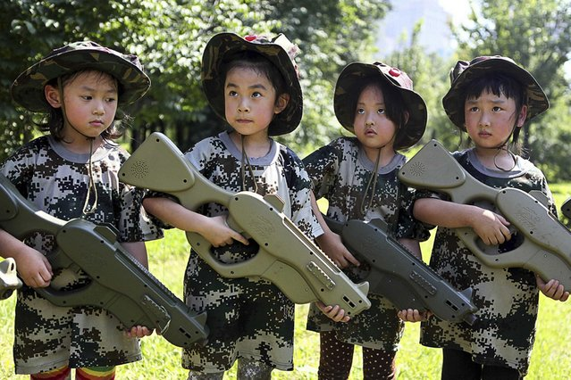 Children holding toy guns participate in an event to simulate military training at a children's activity centre in Shenyang, Liaoning province, China, on August 2, 2013. (Photo by Reuters)