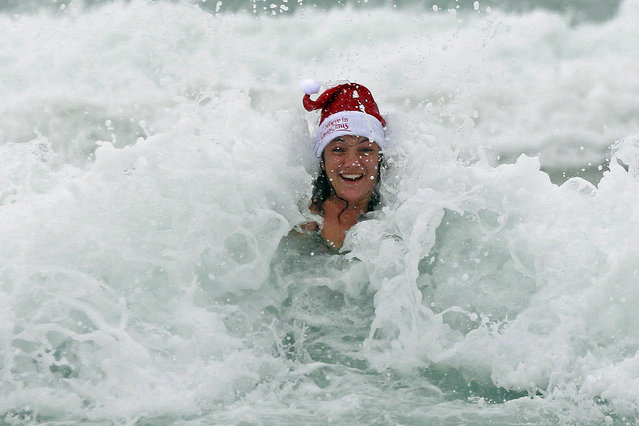 A woman enjoys the waves on a cold and windy Christmas day at Bondi beach in Sydney December 25, 2012. (Photo by Daniel Munoz/Reuters)