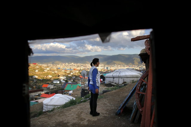 Baljirjantsan Otgonseren, 32, stands outside her family ger, a traditional Mongolian tent, in an area known as a ger district in Ulan Bator June 26, 2013. Approximately 60 percent of the population of Ulan Bator live in settlements known as ger districts and in many cases residents have limited access to basic services such as water and sanitation. According to a 2010 National Population Center census, every year between thirty and forty thousand people migrate from the countryside to the capital Ulan Bator. Ger districts in the city have been expanding rapidly in recent years. Mongolia is the world's least densely populated country, with 2.8 million people spread across an area around three times the size of France. (Photo by Carlos Barria/Reuters)