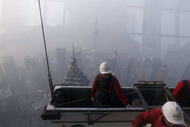 Workers clean the exterior of Shanghai World Financial Center amid heavy smog at the financial district of Pudong in Shanghai, China, December 25, 2015. (Photo by Aly Song/Reuters)