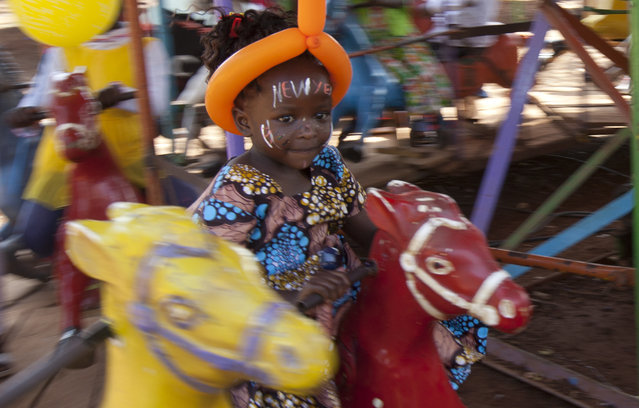 A Kenyan child with a painted face enjoys a ride on a carousel during New Year celebrations at Uhuru Park in Nairobi, Kenya. Monday, January 1, 2018. Hundreds of Kenyans gathered with their children to celebrate at the park. (Photo by Sayyid Abdul Azim/AP Photo)