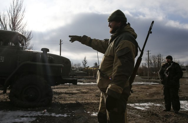 A member of a rebel unit of the self-proclaimed separatist Donetsk People's Republic points to a truck damaged in clashes with the Ukrainian army in the village of Olenivka, south of Donetsk, February 7, 2015. (Photo by Maxim Shemetov/Reuters)