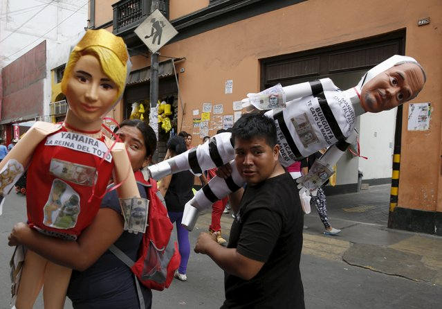 People carry effigies of former President of the Peruvian Football Federation Manuel Burga (R) and Yahaira, a dancer and girlfriend of Peru's soccer player Jefferson Farfan, in a market in Lima, Peru, December 30, 2015. (Photo by Mariana Bazo/Reuters)