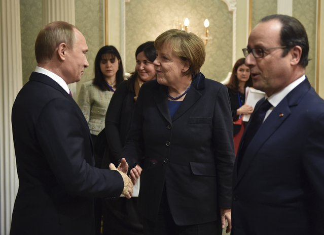 Russia's President Vladimir Putin (L), shakes hands with Germany's Chancellor Angela Merkel as France's President Francois Hollande stands nearby during a meeting on resolving the Ukrainian crisis in Minsk, February 11, 2015. (Photo by Mykola Lazarenko/Reuters)