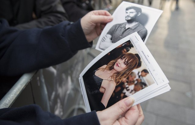 """A fans holds photographs of actors Dakota Johnson and Jamie Dornan at the """"Fifty Shades of Grey"""" film UK premiere in London, February 12, 2015. (Photo by Neil Hall/Reuters)"""