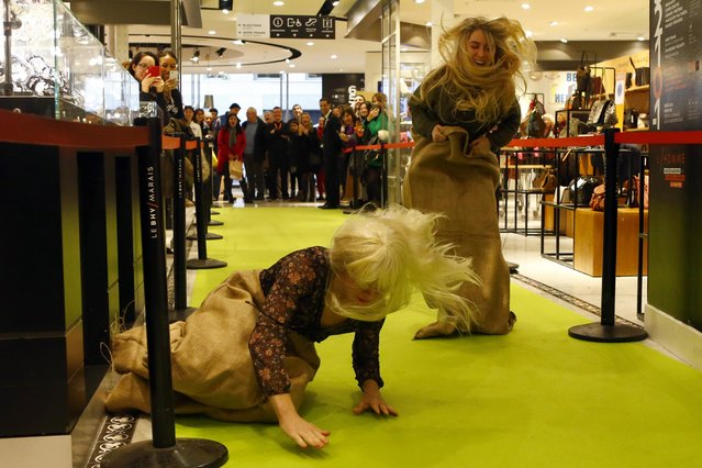 Participants, one of them loosing balance, jump in a sack race at a shopping center in Paris to win a 500 euros voucher (537 USD), on the first day of the winter sales in Paris, France, Wednesday, January 6 , 2016. The five-week 2016 winter sales start everywhere across France on Wednesday jan. 6 and end on Feb. 16. (Photo by Francois Mori/AP Photo)