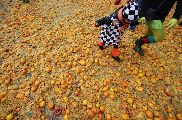 A mother and her child walk during an annual carnival battle with oranges in the northern Italian town of Ivrea February 15, 2015. (Photo by Max Rossi/Reuters)