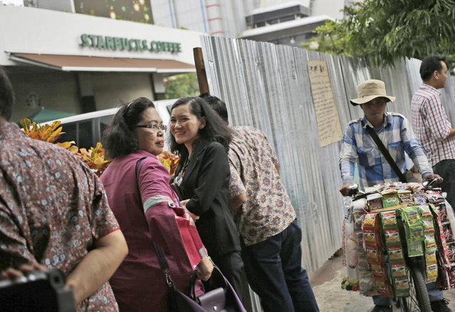 Curious onlookers gather outside the Starbucks cafe where Thursday's attack occurred in Jakarta, Indonesia, on Friday, January 15, 2016. (Photo by Dita Alangkara/AP Photo)