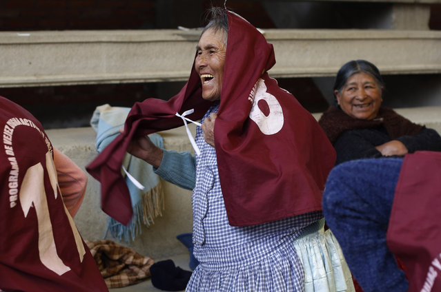 """In this January 28, 2105 photo, 83-year-old Josefina Tito slips a jersey over her dress as she prepares for a handball game with fellow Aymara indigenous elderly women in El Alto, Bolivia. Tito said she's been playing handball for nine years, and that she also plays other sports with her son at home. """"I'm always playing"""" she said. (Photo by Juan Karita/AP Photo)"""