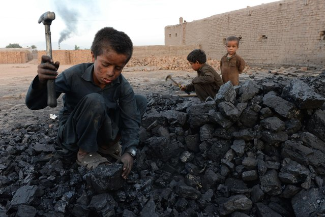 In this photograph taken on April 28, 2018, Afghan children work at a coal yard on the outskirts of Jalalabad, Afghanistan. (Photo by Noorullah Shirzada/AFP Photo)