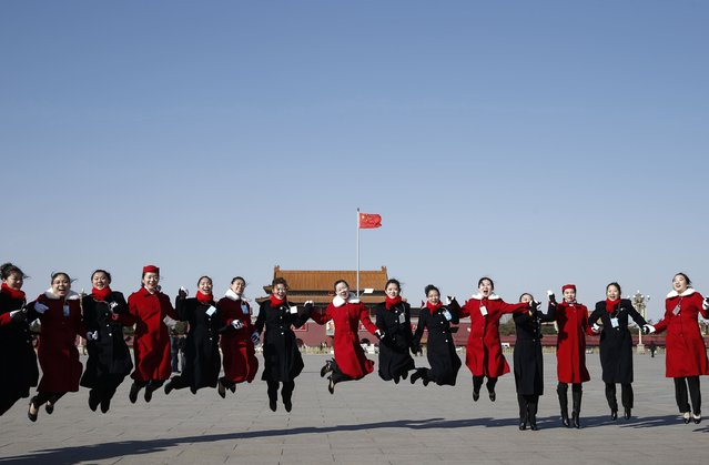 Hotel guides jump during the opening session of the Chinese People's Political Consultative Conference (CPPCC), at Tiananmen Square in Beijing, March 3, 2015.  REUTERS/Kim Kyung-Hoon