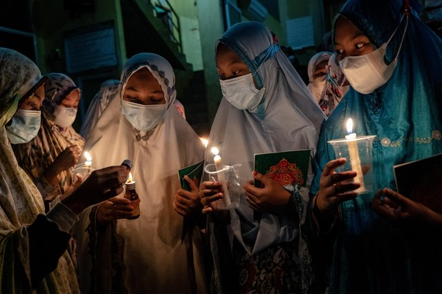 Students wearing protective masks hold candles as they prepare to read the Quran during ritual Nuzulul Koran and Laylat al-Qadr (Night of Destiny) which marks the night in which the holy Quran was first revealed to the Prophet Mohammed at the Nurul Hidayah Al-Mubarokah boarding school on May 2, 2021 in Boyolali, Central Java, Indonesia. Laylat al-Qadr is was one of the odd-numbered nights of the last ten days of Ramadan. Ramadan, the ninth month of the Islamic calendar is a month of fasting, prayers and recitation of the Quran. (Photo by Ulet Ifansasti/Getty Images)