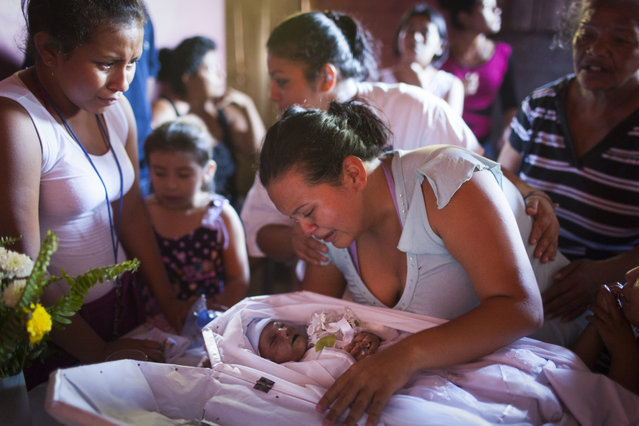 Valeria Michel Hercules lifts up her dead baby, Gabriel Alexander, at a funeral held in the Las Victorias district of San Salvador. It is unclear how he died. His mother, Valeria Michel Hercules, was in prison when she went into labour. The guards allegedly delayed her transfer to hospital despite her appeals. When she finally arrived, the infant was dead and she had to deliver a still born child the next day. (Photo by Adam Hinton)