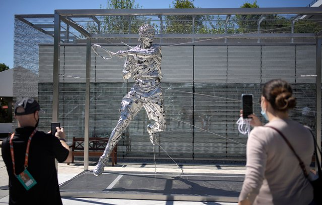 Spectators take photos on their smartphones of a new statue of Spain's Rafael Nadal on day two of the French Open tennis tournament at Roland Garros in Paris, France, Monday, May 31, 2021. (Photo by Christophe Ena/AP Photo)