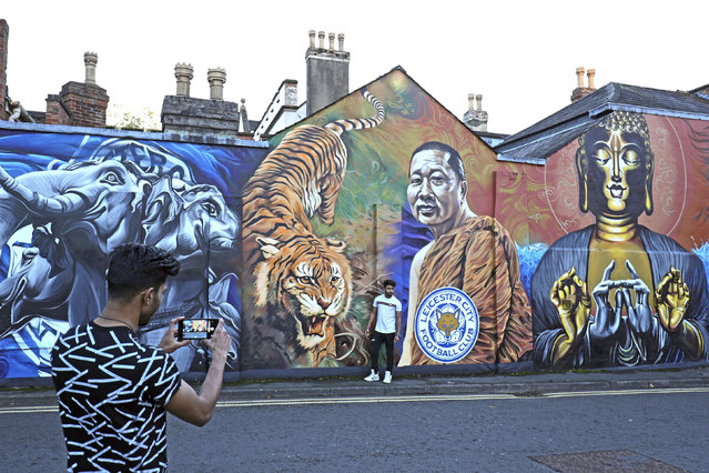 A man takes a photo near a mural of Leicester City's owner, Thai billionaire Vichai Srivaddhanaprabha near the Leicester City Football Club after a helicopter crashed in flames the day before, in Leicester, England, Sunday, October 28, 2018. A helicopter belonging to Leicester City's owner, Thai billionaire Vichai Srivaddhanaprabha, crashed in flames in a car park next to the soccer club's stadium shortly after it took off from the field following a Premier League game on Saturday night. (Photo by Aaron Chown/PA Wire via AP Photo)