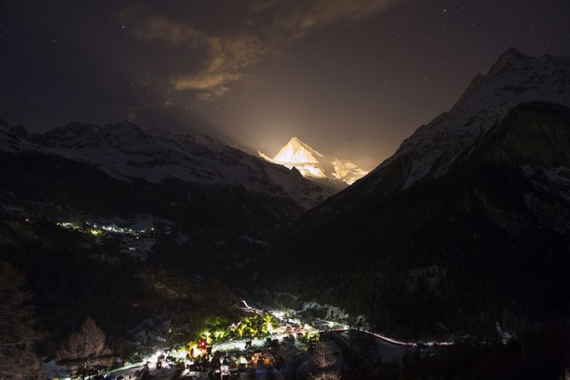 """The Dent Blanche mountain is illuminated with pyrotechnics during the 13 stars on the summit event, in """"Les Hauderes"""" Val d'Herens, Switzerland, Wednesday, March 18, 2015. The 13 stars on the summit event is part of the celebration of the 200th anniversary of Valais membership in the Swiss Confederation. 13 mountains of the Swiss Alps have been illuminated simultaneously during 3 minutes. (Photo by Denis Emery/AP Photo/Keystone)"""