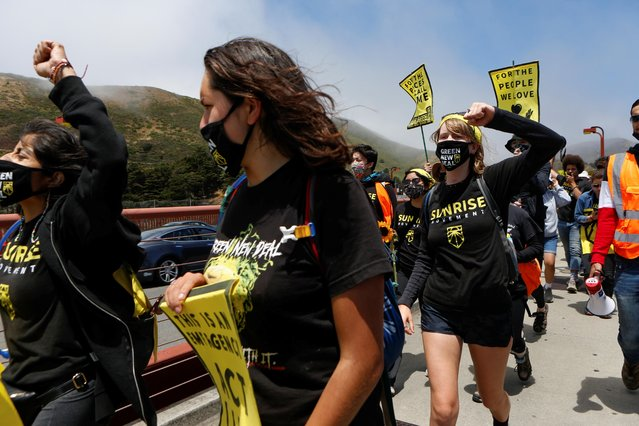 Youth activists, who began their trek in Paradise, California, march across the Golden Gate Bridge to the home of House of Representatives Speaker Nancy Pelosi to highlight their demand of the creation of the Civilian Climate Corps, in San Francisco, California, U.S. June 14, 2021. (Photo by Amy Osborne/Reuters)