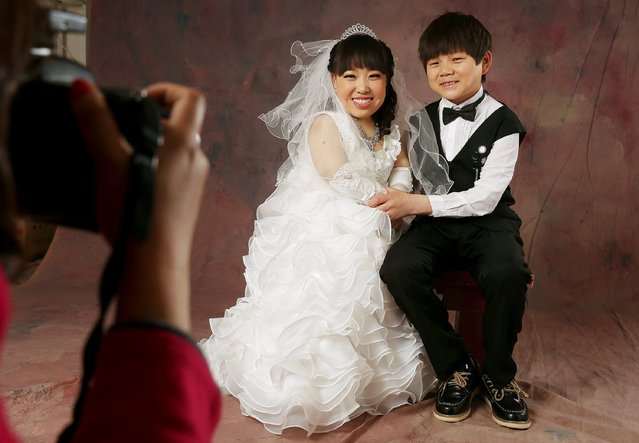 A dwarf couple, Hai Lulu and her fiance, Li Zhouyao, pose for wedding pictures at a studio in Luoyang, Henan province, March 19, 2015. (Photo by Reuters/Stringer)