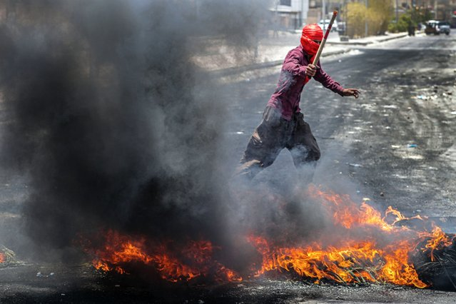 Protesters burn tires to block roads during a demonstration demanding the return of electricity in Basra, southeast of Baghdad, Iraq, Friday, July 2, 2021. A widespread power outage is hitting Iraq as temperatures reach scorching levels, affecting even affluent areas in the capital and stirring concerns of widespread unrest. (Photo by Nabil al-Jurani/AP Photo)