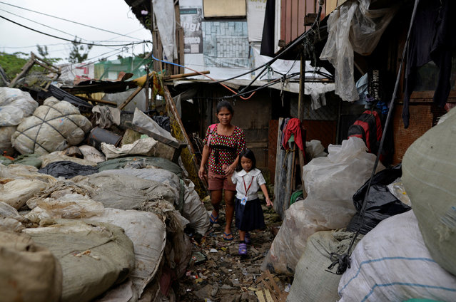 """Weng Ruda, 36, mother of three walks her daughter to school at a slum area in Quezon city, Metro Manila, Philippines October 13, 2016. """"I like that he is very tough. There are no children loitering around now. They also avoid picking up bad habits"""", she said. (Photo by Ezra Acayan/Reuters)"""