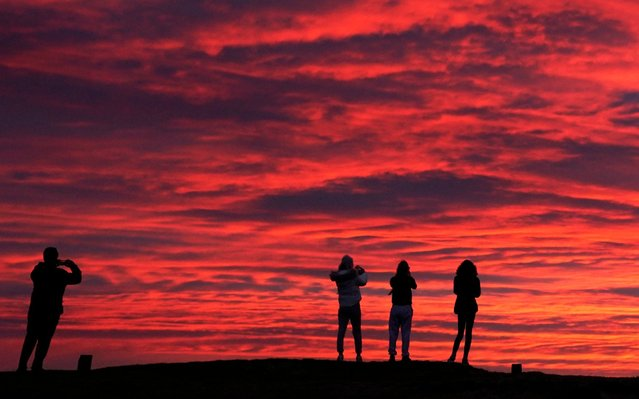 People are silhouetted against the stunning red sky at sunrise in Blyth, Northumberland on Tuesday February 23, 2021. (Photo by Owen Humphreys/PA Images via Getty Images)