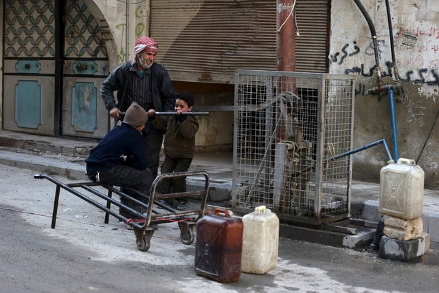 Residents push a lever to fill water containers in Douma, Syria February 3, 2016. (Photo by Bassam Khabieh/Reuters)