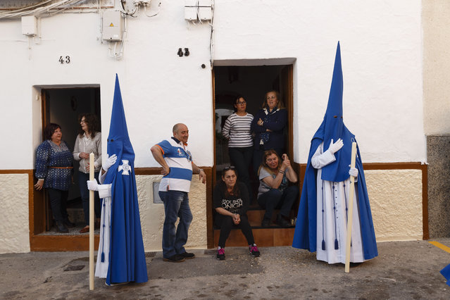 "People look from their house as penitents take part in ""Nuestro Senor Atado a la Columna, Maria Santisima de la Paz y San Juan Evangelista"" Holy Week procession in Arcos de la Frontera, Spain, Tuesday, March 31, 2015. (Photo by Daniel Ochoa de Olza/AP Photo)"
