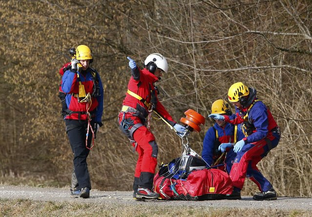 Members of emergency services prepare an injured person for transportation by helicopter from the site of the two crashed trains near Bad Aibling in southwestern Germany, February 9, 2016. Several people died after two trains collided in the southern German state of Bavaria on Tuesday, a police spokesman said, adding about 100 people were also injured. (Photo by Michael Dalder/Reuters)