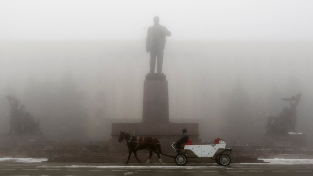 A man rides on a horse cart past a monument of Soviet State founder Vladimir Lenin on a central square during a foggy day in Stavropol, southern Russia December 29, 2016. (Photo by Eduard Korniyenko/Reuters)