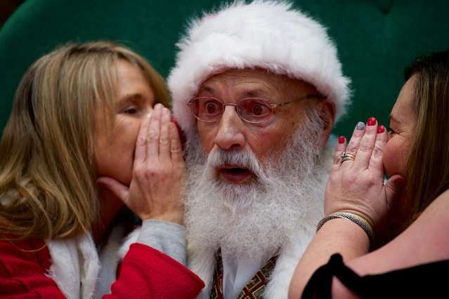 Santa Claus reacts as (L) Tami McEleney and (R) Patrice Conner whisper in his ear at the King of Prussia Mall, United States' largest retail shopping space, in King of Prussia, Pennsylvania, U.S., December 8, 2018. (Photo by Mark Makela/Reuters)