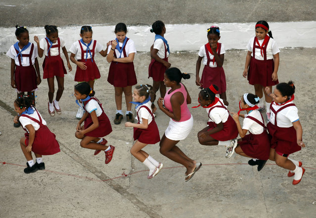 School children play with their teacher during recess at Martires de Tarara primary school in Havana,  November 2009. (Photo by Desmond Boylan/Reuters)