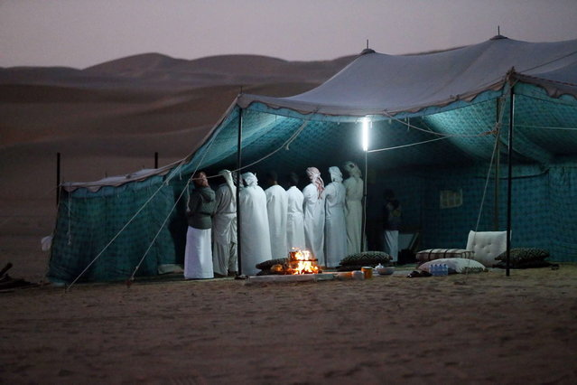 Emiratis gather for prayer inside a tent at the Liwa desert, 220 kms west of Abu Dhabi, on the sidelines of the Mazayin Dhafra Camel Festival on December 21, 2013. (Photo by Karim Sahib/AFP Photo)